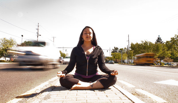 Monique Dauphin doing sukhasana in a busy street