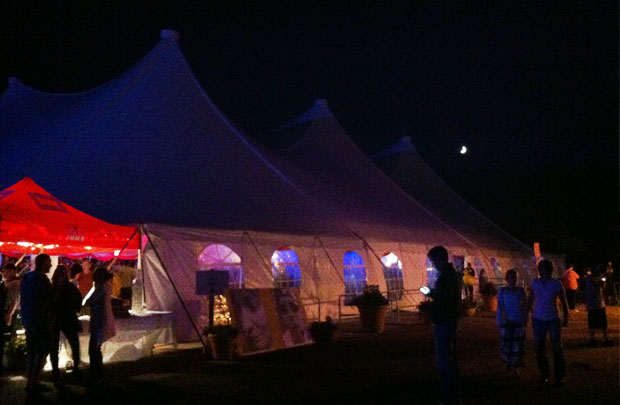 The moon shines above the big tent.